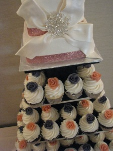 Top tier cake covered in buttercream with fondant bow/ribbon, cupcakes with buttercream roses.